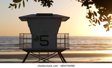 Lifeguard watch tower, sunny sunset beach, Oceanside USA. Rescue station, waterfront watchtower hut and tree leaves, pacific ocean coast atmosphere. California summertime aesthetic, Los Angeles vibes.