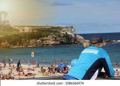 A lifeguard watching over the world famous Bondi Beach, which is very crowded. The sunny coast side in Sydney, Australia is a very big touristical attraction.A green cliff is visible in the background