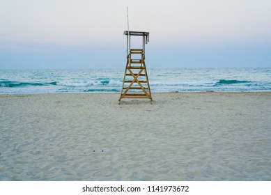 Lifeguard watchtower on the beach at sunset.