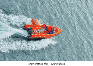 Lifeguards in orange jackets in the boat in the open sea.