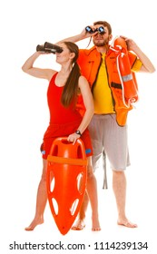 Lifeguards with rescue tube ring buoy lifebuoy and life vest jacket looking through binoculars. Man and woman supervising swimming pool. Accident prevention.