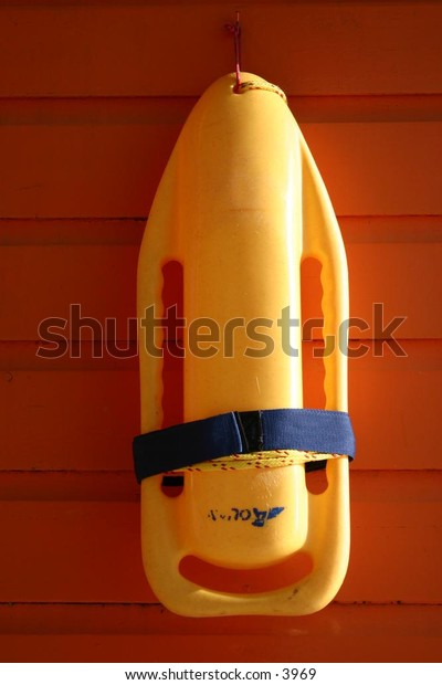 a lifeguard's tool - yellow preserver on the wall
