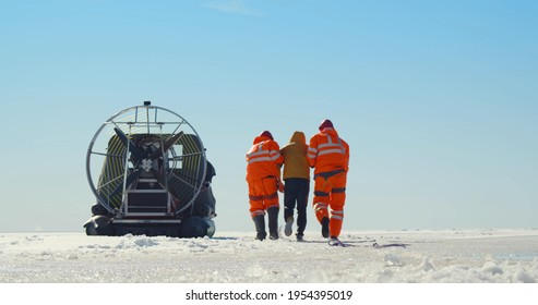 Lifesavers with rope pulling drowning man out of icy water in winter. Team of professional coast guards rescuing sinking man in arctic