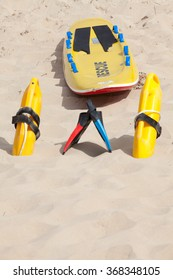 Lifesaving raft, floatation devices and swimming fins lying on beach in summer sun
