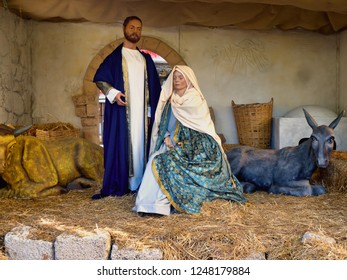Life-sized nativity scene in Santa Cruz de Tenerife on Tenerife. Mari and Josef and a donkey. Mary sits on a hay bale filled with noble robes and Josef stands next to her with a dark blue open coat.