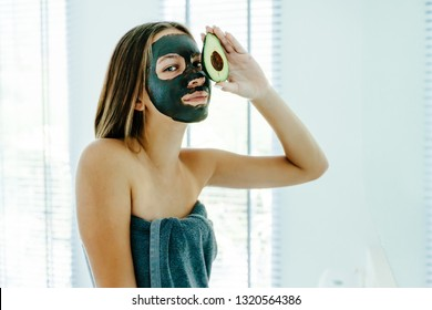 Lifestyle of 12-14 years old teen girl applying black clay facial mask with avocado. Teenage girl wrapped in towel doing organic anti blemish skin care routine in bright bathroom after morning shower.