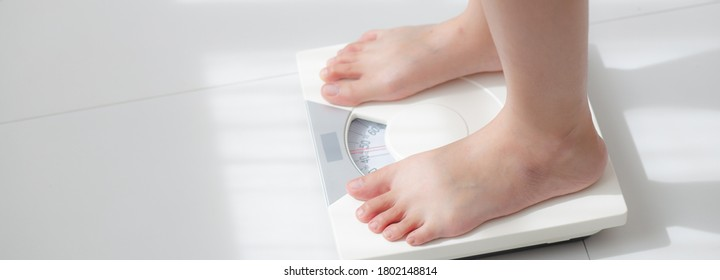 Lifestyle activity with leg of woman stand measuring weight scale for diet with barefoot, closeup foot of girl slim weight loss measure for food control, healthy care concept, banner website.
