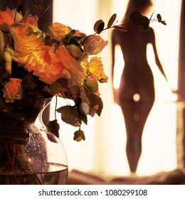 Lifestyle art photo of beautiful sensual blonde with flowers at the window. Home interior. Beautiful morning. Aroma bouquet. Perfume