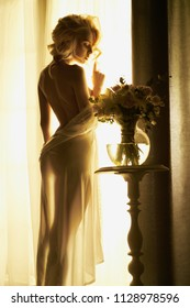 Lifestyle art photo of beautiful sensual blonde with flowers at the window. Home interior. Beautiful morning