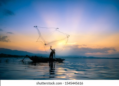 Lifestyle of Asian fisherman on wooden boat for catching freshwater fish in reservoir in the early morning before sunrise