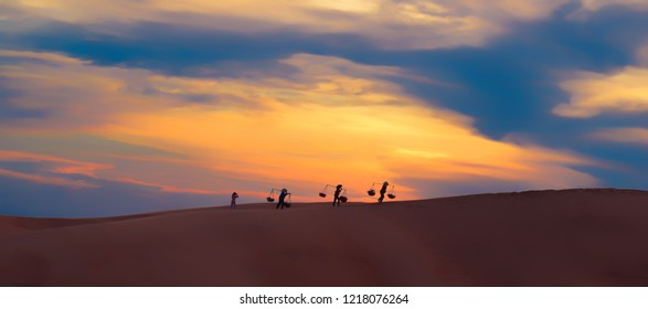 Lifestyle of Asian women carrying baskets on her shoulders in the desert at sunset or sunrise time, Mui Ne, Vietnam.Asian women is walking and carry basket.