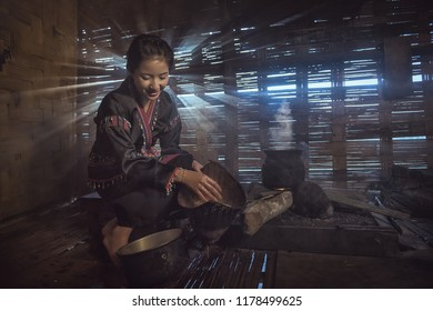 Lifestyle of Asian women in the field countryside Laos. Woman is blowing the fireplace for cooking in traditional kitchen.