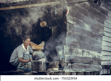 Lifestyle of Asian women in the field countryside Thailand.woman is blowing the fireplace for cooking in traditional kitchen.Thailand village women cooking in traditional kitchen on the morning.