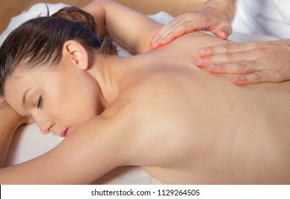 lifestyle, attractive spanish brunette girl getting a naked back massage by a massage professional
