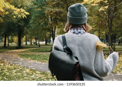 Lifestyle autumn portrait from the back of young adult female in forest or park in hat and denim jacket, selective focus