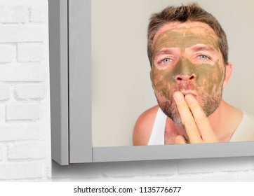 lifestyle bathroom mirror portrait of young attractive happy man with green cream on his face applying facial mask sending kiss to his reflection feeling conscious in male cosmetics concept