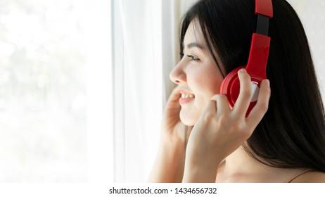 Lifestyle Beautiful asian woman cute girl  feel happy enjoy listening to music with earphones headphones on white bedroom