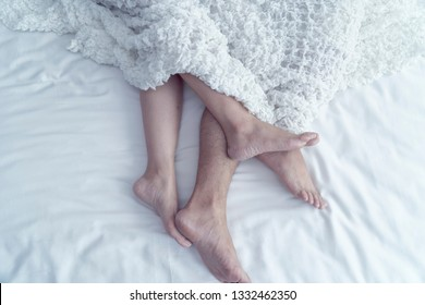 Lifestyle. Beautiful couple in bed. Close up of male and female feet on a bed. Loving couple under white sheets in the bedroom. Concept of sensual and intimate moment of lovers Focus on male foot.