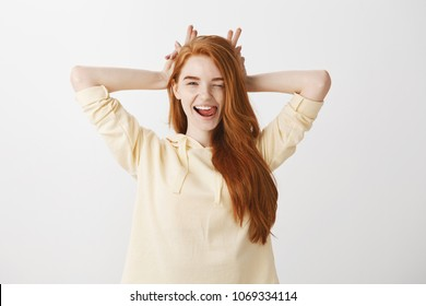 Lifestyle and beautiful people concept. Indoor shot of expressive stylish woman with red hair winking flirty and holding fingers behind head like bunny ears or horns, showing tongue while flirting