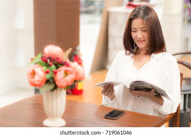 Lifestyle of Beautiful Woman is Reading a Magazine with Flower Vase on Table. Asian Female Model Portrait Close up Concept. Copy Space for Text.