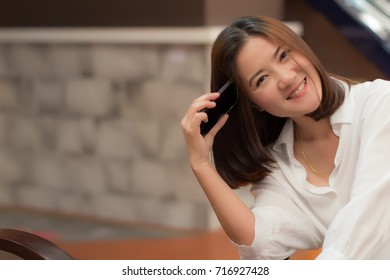 Lifestyle of Beautiful Woman is Talking on a Smart Mobile phone. Asian Caucasian Female Model Portrait Close Up Concept. Copy Space for Text.
