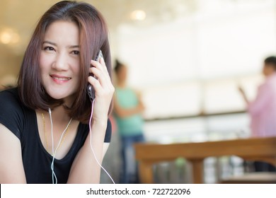 Lifestyle of Beautiful Woman is Using Smart Mobile phone and Wearing Earphones in Coffee Shop. Asian Female Model Portrait Close Up Concept. Copy Space for Text.