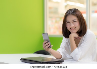 Lifestyle of beautiful working woman is holding smart mobile phone in office with laptop foreground. asian caucasian female model portrait close up concept. copy space for text.