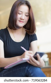 Lifestyle of Beautiful Working Woman is Writing Something in Notebook While Holding  Smart Mobile phone.Asian Female Model Portrait Close Up Concept. Vertical Style