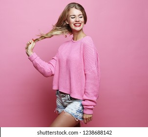 lifestyle, beauty and people concept: Young cute smiling blond girl over pink background