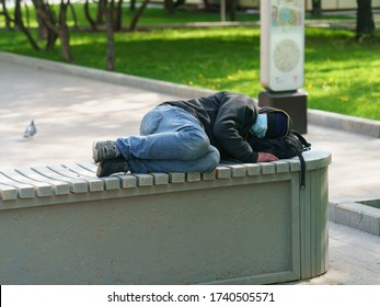 Lifestyle of the big city during coronavirus pandemic time. Using protective facial masks. Spring sunny day. Homeless man  wearing medical mask and sleeping at thecity street