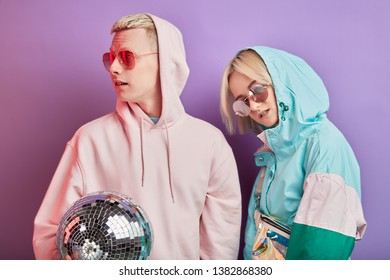 Lifestyle blonde couple looking confidently at camera, wearing sport hic clothes with hood on head, in trendy colores, posing at camera with disco ball. Leisure, entertainment and sport concept.