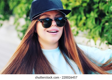 Lifestyle bright urban portrait of pretty girl wearing swag cap and sunglasses.