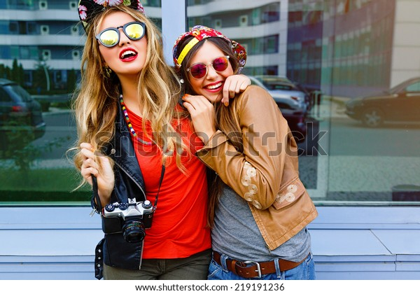 Lifestyle bright urban portrait of two bear fiends. Two pretty girls wearing swag hipster neon hats and sunglasses, hugs and having great time together, city window background.