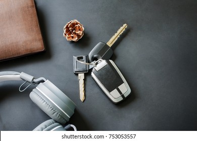 Lifestyle changes of your with stopped work and get out travelling relaxing searching for freedom. above view key car and headphone music and wallet on black table. copy space used for add messages.
