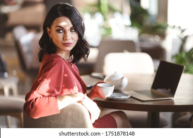 lifestyle and citylife - beautiful brunette business lady in modern gems and fashionable burgundy dress having a lunch in cafe. Woman sits by the table and holds cup of tea