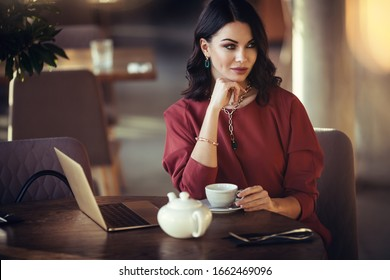 lifestyle and citylife - beautiful brunette lady closeup portrait in modern gems and burgundy dress in cafe interior