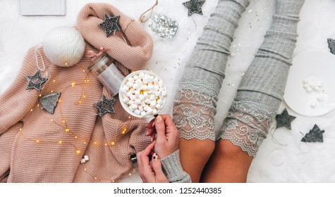 Lifestyle composition. Cozy winter,, warm woollen socks. Woman on white blanket with marshmallow cup and christmas decorations. Holiday relax.