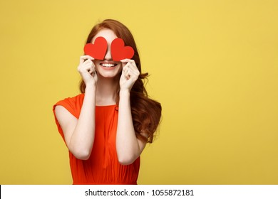 Lifestyle Concept: Attractive woman with beaming smile having two small red hearts in hands, closing eyes with paper heart symbols while standing over yellow background.