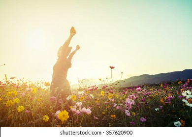 lifestyle concept - beautiful happy woman enjoying fresh air in cosmos flower field