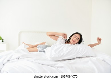 Lifestyle Concept. Cute Asian girl in night dress. Beautiful asian woman is relaxing in a white bedroom. Beautiful asian woman  is sleeping in the morning.