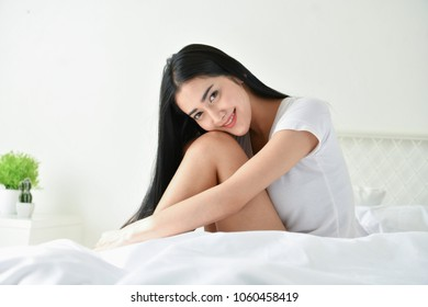 Lifestyle Concept. Cute Asian girl in night dress. Beautiful asian woman is relaxing in a white bedroom. Asian girls are playing in the bedroom happily.