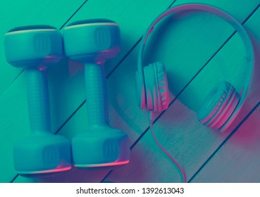 Lifestyle concept. Dumbbells with headphones on wooden background. Retro wave, blue red neon light, ultraviolet. Top view, minimalism
