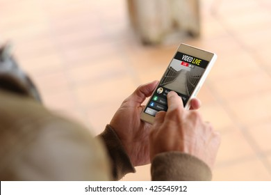 lifestyle concept: Hands male with smartphone watching a live video. All graphics on the screen are made up.