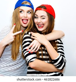 Lifestyle crazy portrait of sisters best friends girls hugs, and having fun together, trendy hipster sportive hats and clothes, right make up, blonde and brunette, showing tongue and winking.