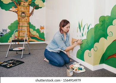 Lifestyle creative hobby and freelance artistic work side job concept. Caucasian woman artist hand painting murals on walls indoor at apartment or studio school with acrylic paints.
