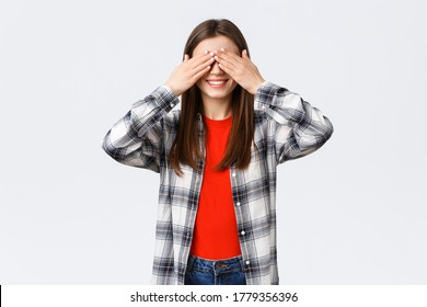 Lifestyle, different emotions, leisure activities concept. Excited happy young relaxed woman promise not peek. Woman cover eyes with palms, playing hide n seek or waiting for surprise