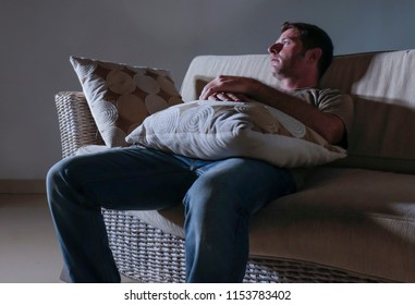 lifestyle dramatic light portrait of young sad and depressed man sitting at shady home couch in pain and depression feeling lost looking away thoughtful and pensive suffering anxiety problem