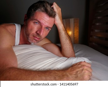 lifestyle dramatic night portrait of attractive desperate and depressed middle aged man unable to sleep suffering anxiety crisis and depression feeling overwhelmed and frustrated in bed