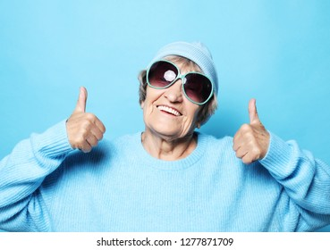 Lifestyle, emotion and people concept: Funny old lady wearing blue sweater, hat and sunglasses showing victory sign.