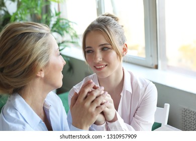 lifestyle, family and people concept: Happy young woman and her mother at home
